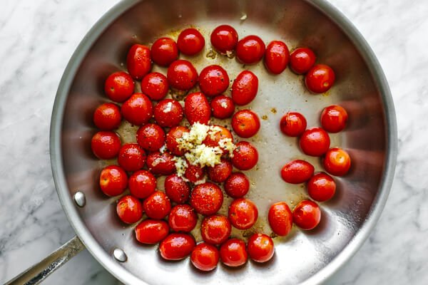 Cooking cherry tomatoes in a pan for blistered tomatoes.