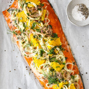 Slow roasted salmon with fennel and orange and herbs next to a fork.