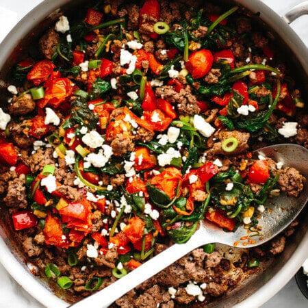 A stainless steel pan with Mediterranean ground beef stir fry