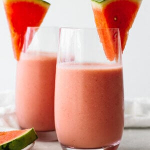 Two glasses of watermelon smoothie with fresh watermelon slices.