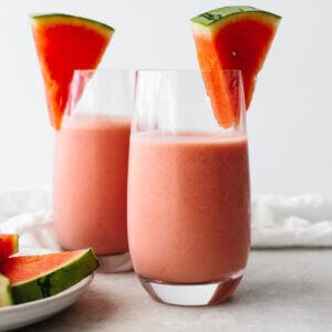 Two glasses of watermelon smoothie next to watermelon slices