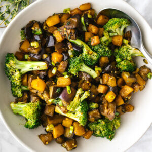 A bowl of eggplant and butternut squash stir fry next to a napkin