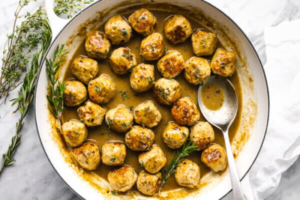 A large pan filled with turkey meatballs in a maple mustard sauce