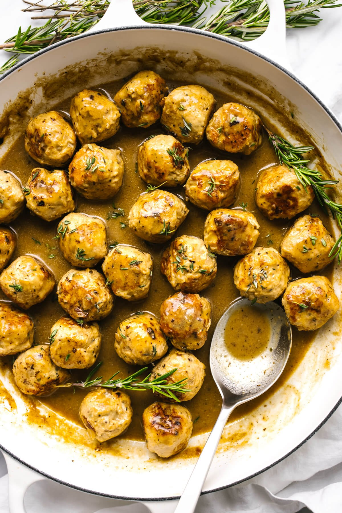 Turkey meatballs in a pan with maple mustard sauce with a spoon.