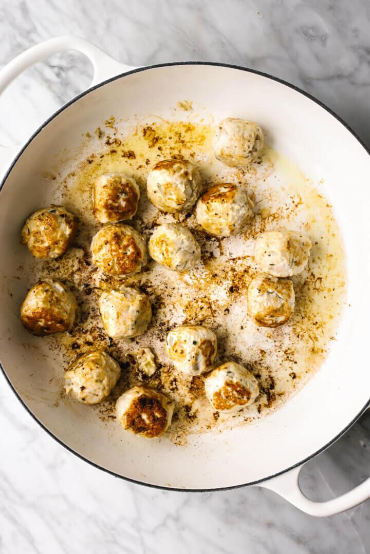 Searing turkey meatballs in a pan