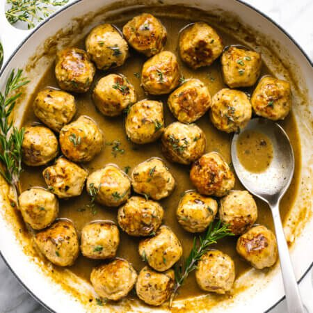 a large pan with turkey meatballs next to fresh herbs